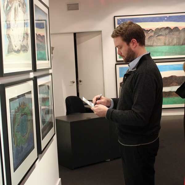 "Brad putting final touches on the exhibition ""Imagined Landscapes: Drawings by Ohotaq Mikkigak -"