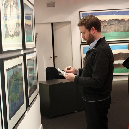 """Brad putting final touches on the exhibition """"Imagined Landscapes: Drawings by Ohotaq Mikkigak -"""
